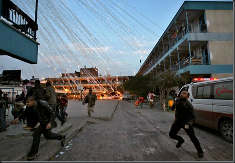 Palestinian civilians and medics run to safety during an Israeli strike over a UN school in Beit Lahia, northern Gaza Strip